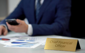 """Person sitting at a desk with a """"Chief Financial Officer (CFO)"""" sign in front of them."""